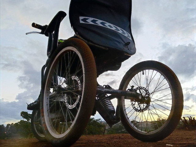 Linccel off-road wheelchair with sun setting in the background and cloudy skies.