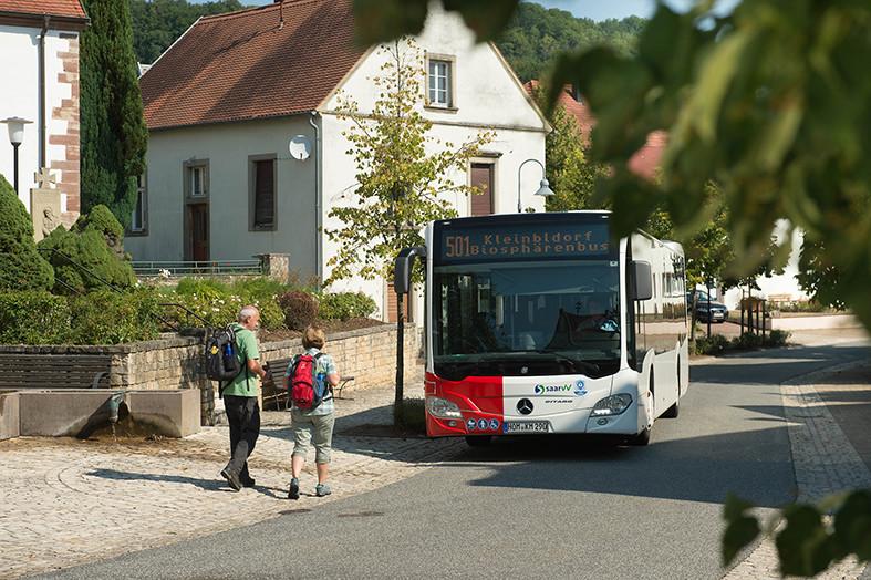 Zwei Teilnehmer steigen in dem rot-weißen Safari-Linienbus, der im Ort steht.