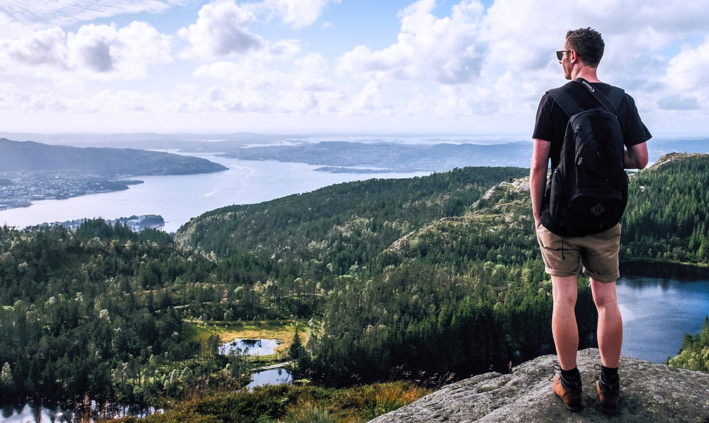 Wanderer blickt von einem Aussichtspunkt über die Natur.