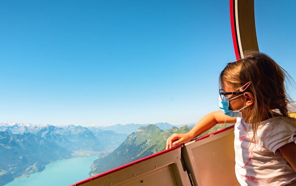 Mädchen sitzt mit Mundschutz in einer Gondel und blickt auf eine Gebirgslandschaft.