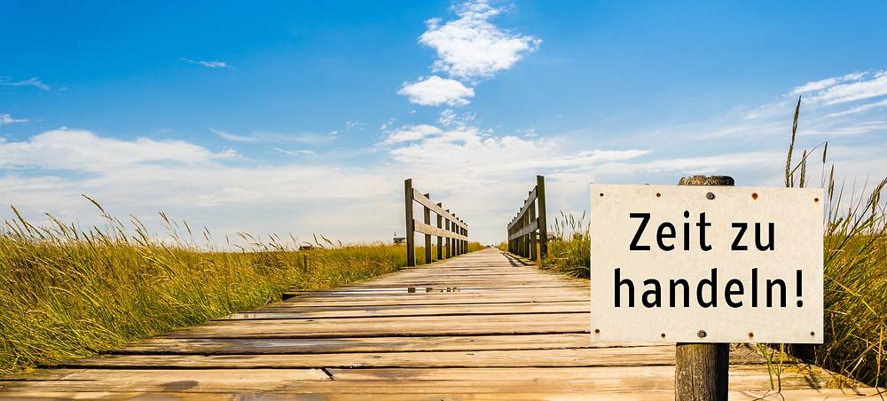 """Schild mit der Aufschrift """"Zeit zu handeln"""" vor einem Holzsteg am Meer."""