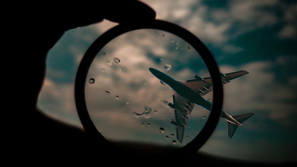 Vergrößerungsglas, das auf ein Flugzeug am Himmel gerichtet ist.