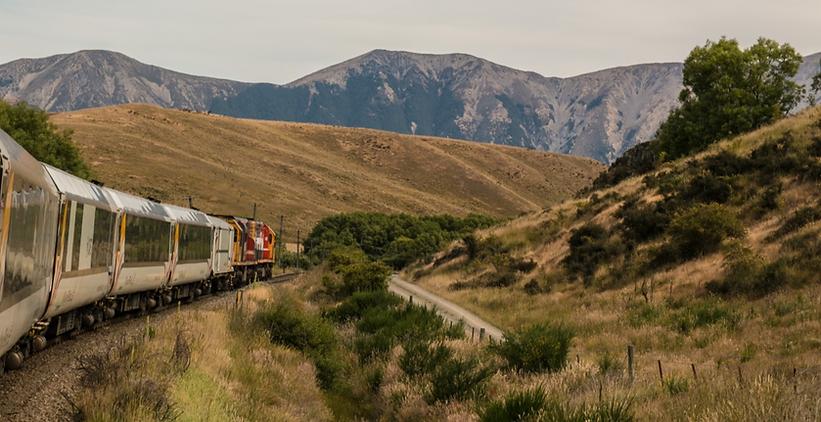 Zug fährt durch Gebirgslandschaft