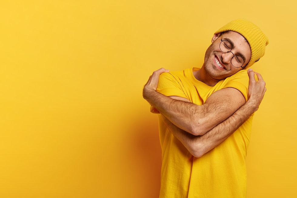 pleased-caucasian-man-hugs-himself-has-h