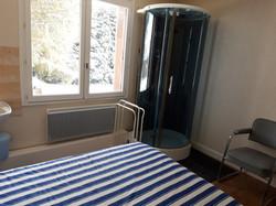 Chambre avec lit double et cabine douche
