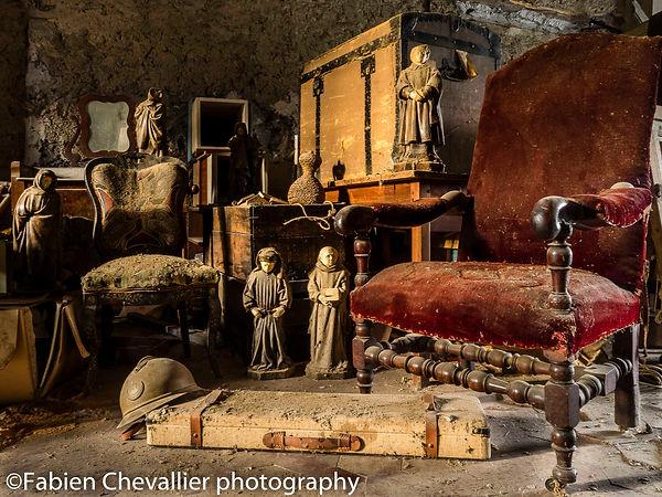 belle photo d'un grenier abandonnée avec des statues ,casque militaire et fauteuil