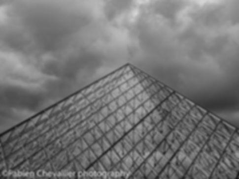 photo noir et blanc de la pyramide du musée du louvre à Paris