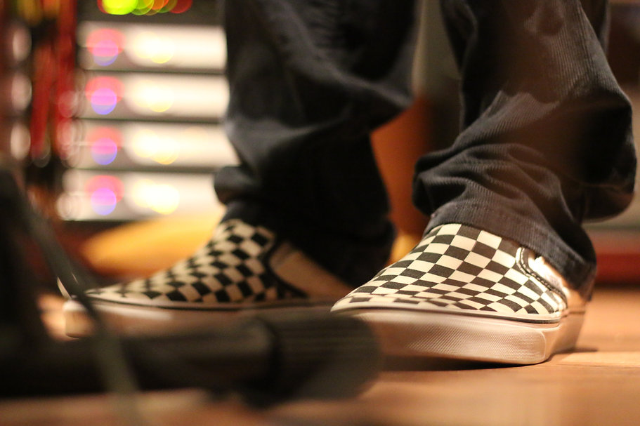 checkerboard Vans on a band leader playing keyboard