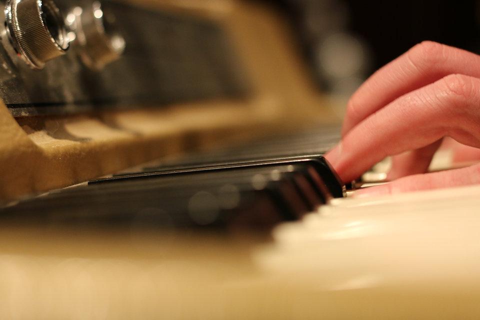 hands on a Wurlitzer keyboard recording original music