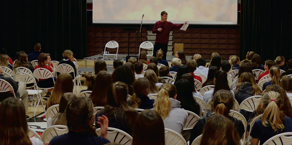 Public speaker with autism holding a audience of studentts in rapt attention