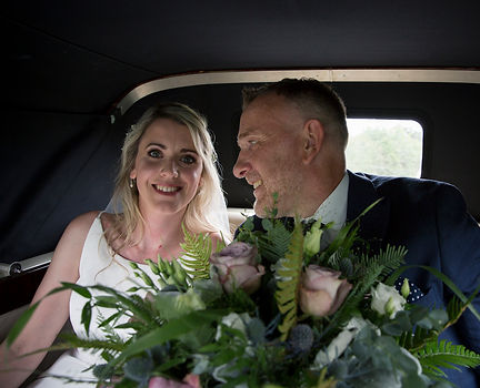 father of the bride smiling at bride in wedding car on way to wedding