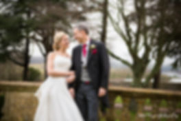 bride and groom smiling at each other, leaning against pillars, happy couple coombe lodge, winter wedding