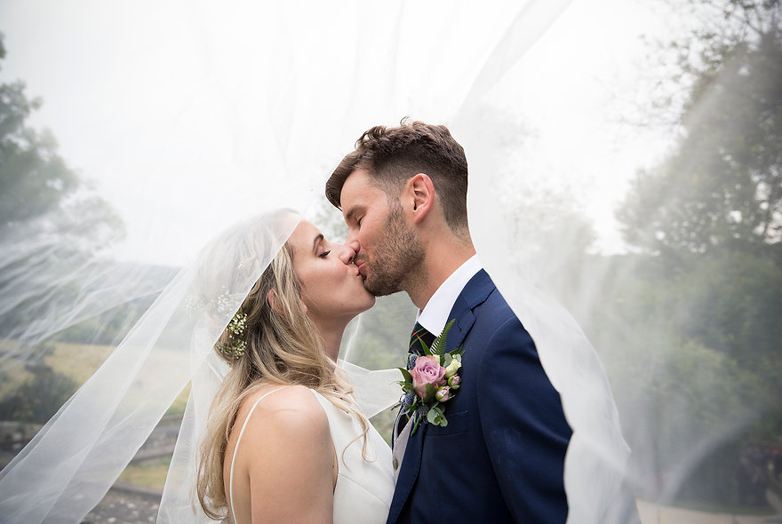 bride and groom kissing under veil, very happy and in love