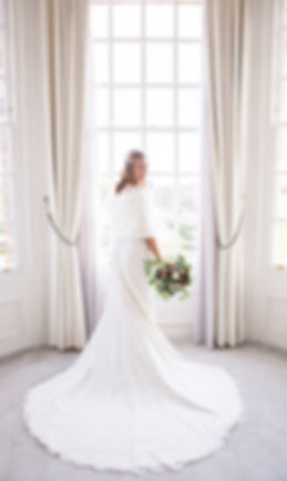 bride in bay window with wedding dress fanned out