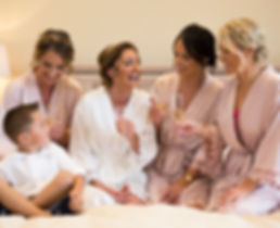 Bride and bridesmaids drinking fizz on bed