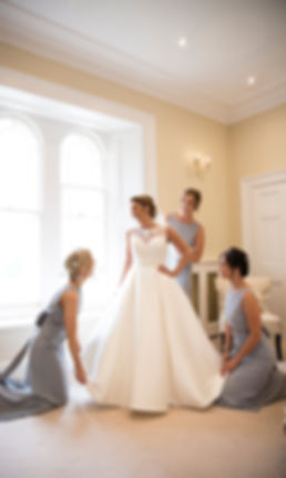 bride and brides maids having fun, bridal prep, just put on weddng dress