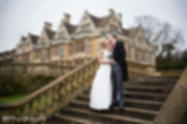 bride and groom kissing coombe lodge in the background, stunning wedding venue, blonde bride on stairs