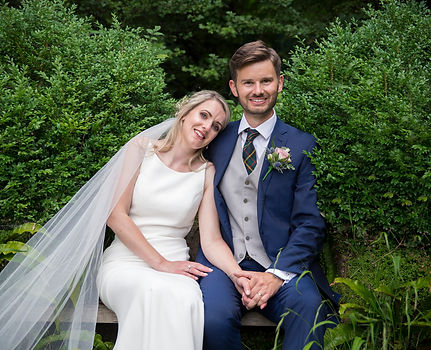 newly weds sat on bench with foliage around