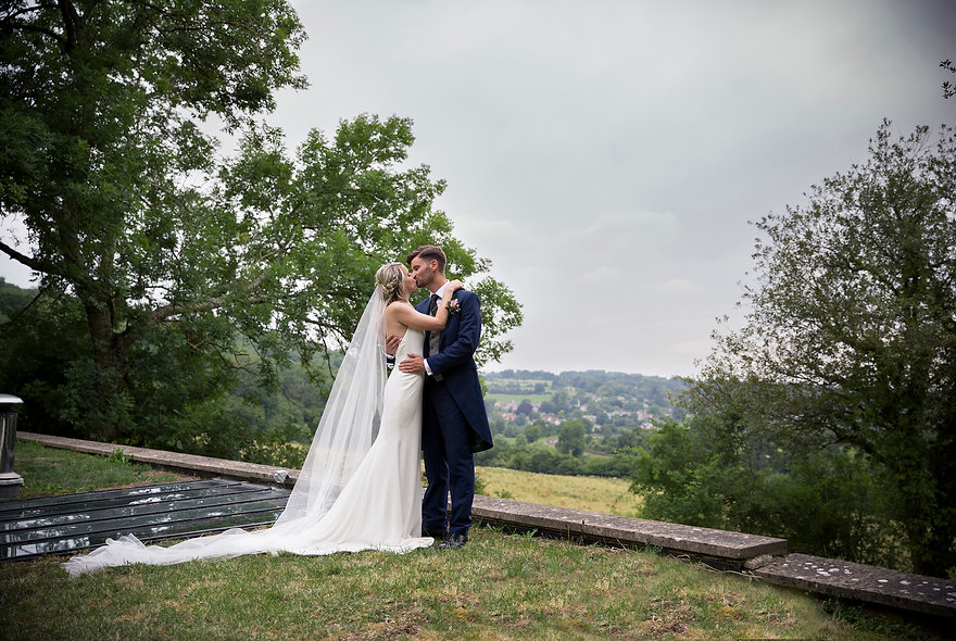 bride and groom on the roof with Bath in the distance, kissing