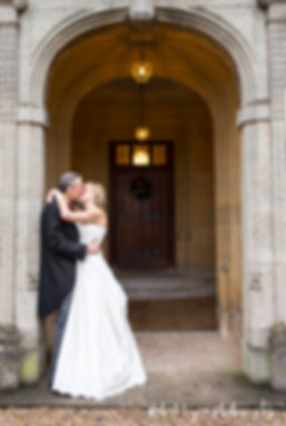 wedding photographer coombe lodge, Kissing in arch, wedding, bride and groom coombe lodge