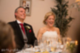 bride and groom laughing at best man speech, hilarious