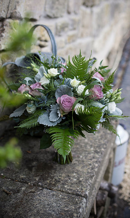 brides bouquet by stone wall