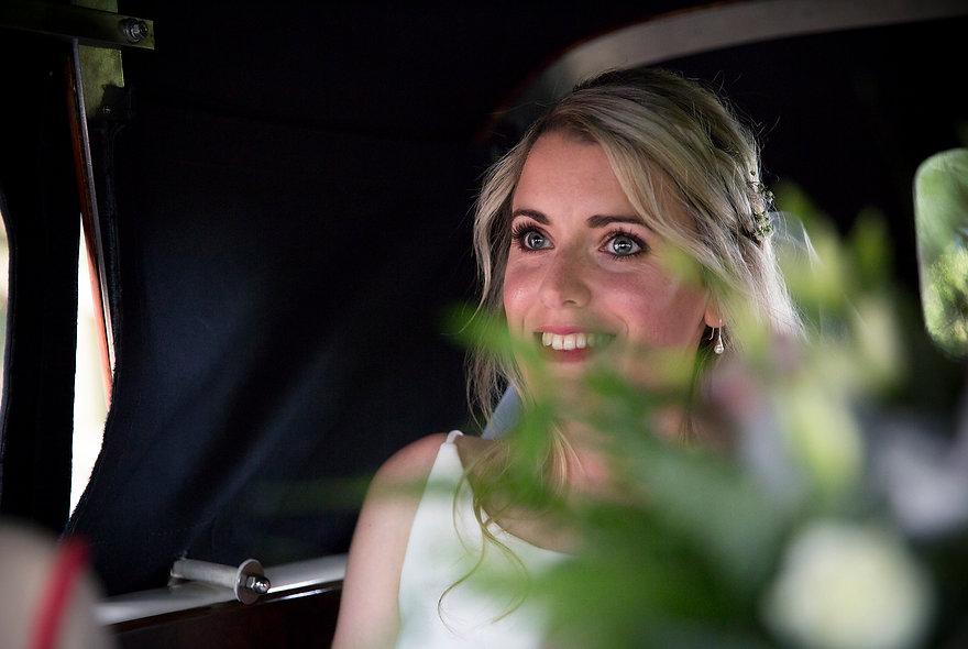bride in wedding car on way to wedding, smiling bride