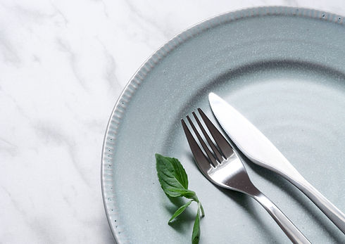 Empty light blue plate on a white marble counter with a knife and fork beside a mint leaf