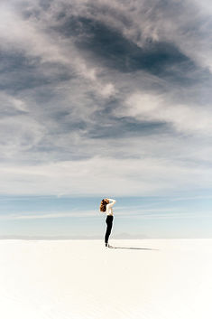 Lady standing on sand looking up towards the sky