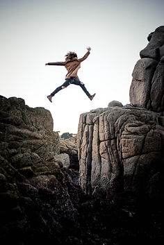 Person leaping across a rocky divide