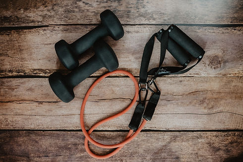 Black handheld weights and an orange exercise band on a wooden background