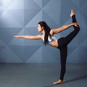 Woman with long brown hair doing yoga pose in black yoga pants and white sports bra