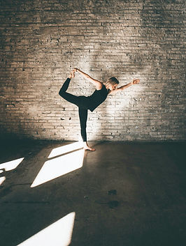 Woman doing a standing yoga pose by a brick wall