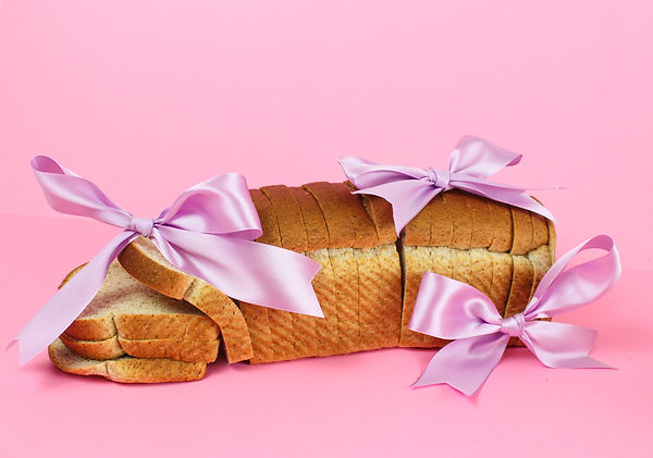 A loaf of bread on a pink background, the bread is covered in three silk purple bows and the left side of the loaf is tipped over.