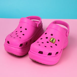 "A pair of hot pink Croc shoes on a pink foreground with a blue background. There is a bread charm on the right Croc shoe that states ""Let's Get This Bread"""