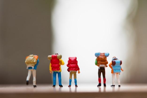 [Fotografia] Cinco bonequinhos em miniaturas, mochileiros, estão de costas, o fundo está desfocado.