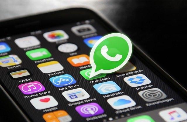 [Fotografia e montagem] Tela de celular com diversos aplicativos na tela inicial. O logo do Whatsapp salta da tela em destaque.