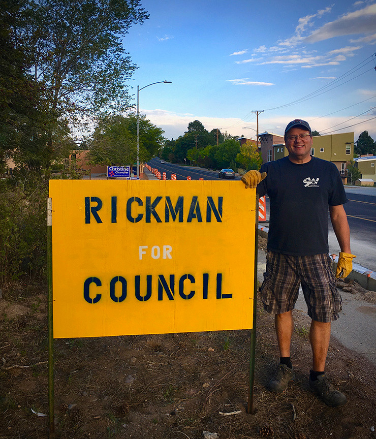 Candidate James Rickman standing next to a sign supporting his candidacy