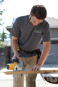 Carpenter using saw to work on construction project