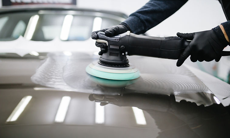 Car detailing - Man with orbital polisher in repair shop polishing car. Selective focus..j