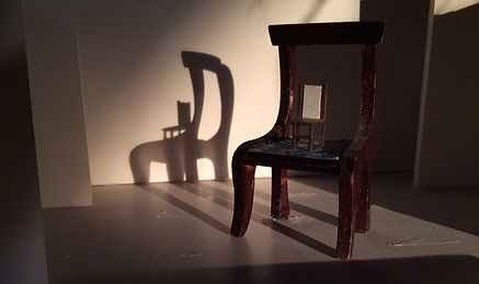 Miniature chair on top of miniature chair in stagelight