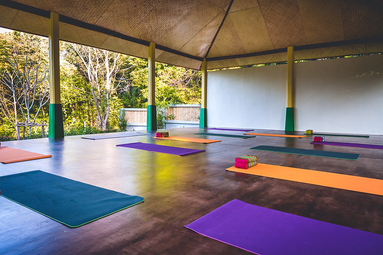 Image of Lanta Yoga Shala set in tropical gardens. Text reading Disappear into the sound of your own breath.  Koh Lanta, Thailand