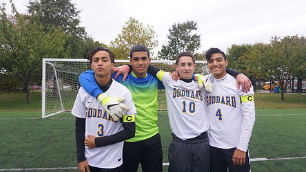 4 boys in soccer uniform on field