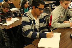 Students in classroom writing on paper