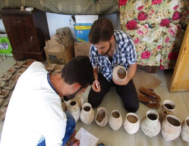 Members of the Idlib Antiquities Center recording critical information about the tomb's pottery.
