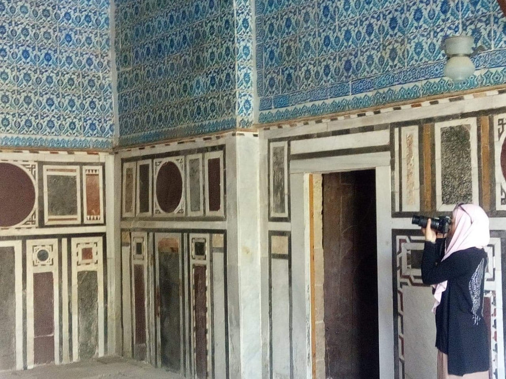 A member of the Al-Darb Al-Ahmar Monuments Project photographs the blue-tiled walls of Cairo's Blue Mosque.