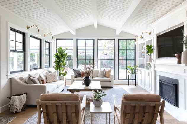 Living room with vaulted ceilings and black windows by Cabana Rehab Interiors