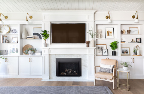 Marble fireplace surround with white built-ins by Cabana Rehab Interiors