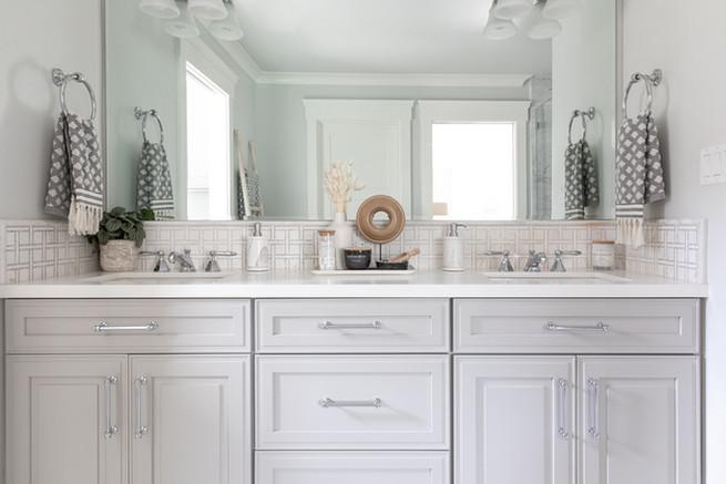 Grey bathroom cabinets with marble backsplash