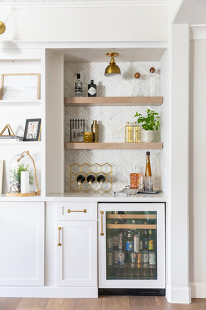 Living room built-ins with dry bar and marble herringbone backsplash